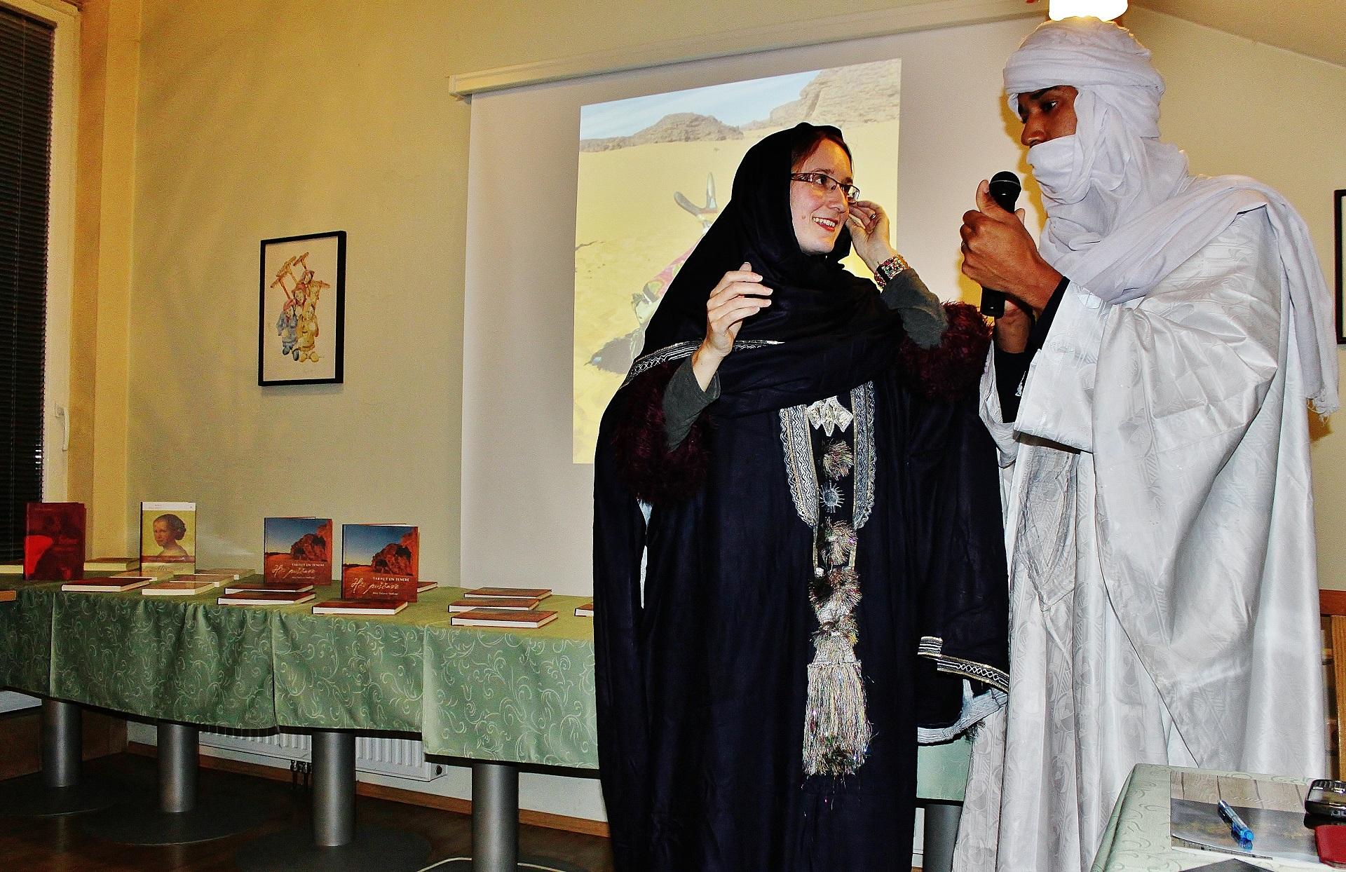 Mira v pogovoru z Abdelom. V ozadju knjige o Tuaregih in prvi slovenski pesnici,pisateljici in skladateljici Josipini Urbačič Turnograjski.