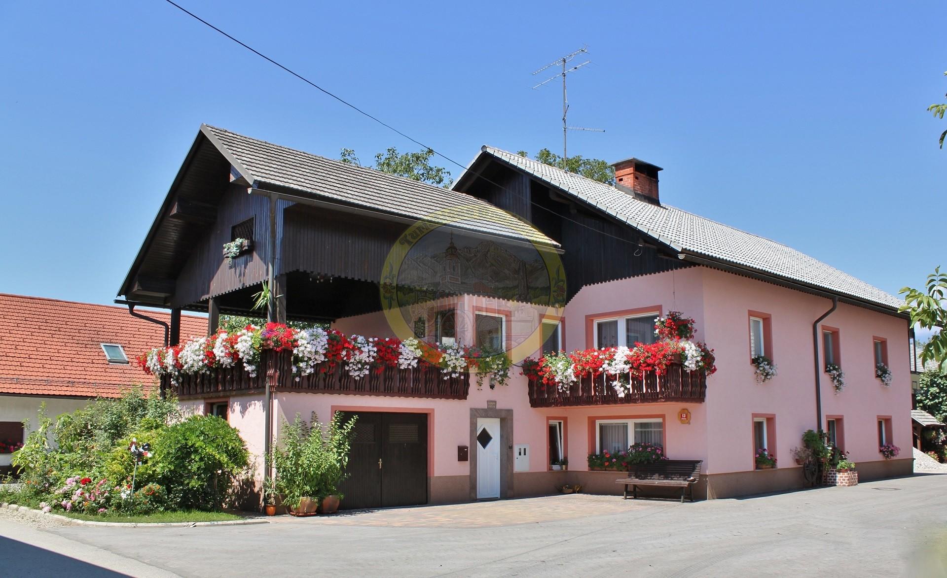 Jurjevčeva kmetija na Okroglem je med najlepšimi v vasi. Posebej lepa je hiša s slapovi rož.